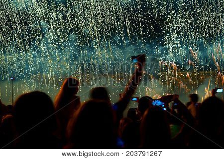Colorful fireworks, as big silver rain or Bisser, litle beads . Unrecognizable silhouette back to us. Explosive pyrotechnic devices for aesthetic and entertainment purposes, art