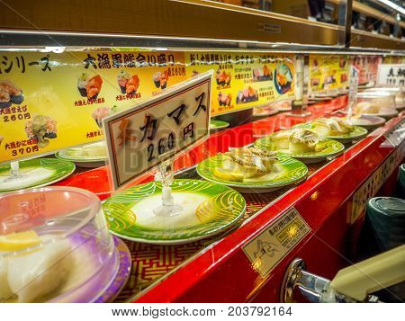 TOKYO, JAPAN -28 JUN 2017: Close up of assorted japanesse food over a table, inside of a kaitenzushi conveyor belt sushi restaurant in Tokyo, Japan.