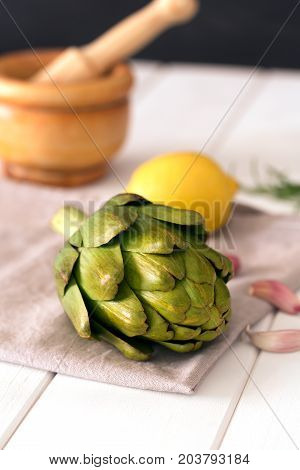 Artichokes and lemons on wooden table. Ready to be prepared as natural healthy food