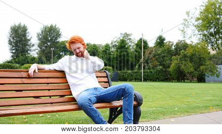 Tired Man With Neck Pain, Red Beard And Hairs, Sitting In Park On Bench