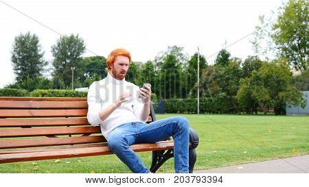 Failure, Loss Gesture By Man Using Smartphone, Sitting On Bench Outdoor