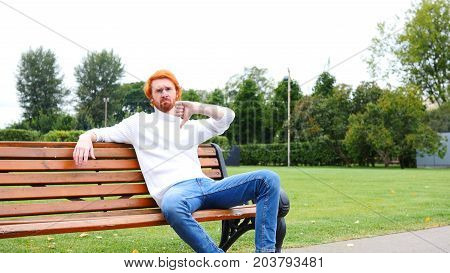 Thumbs Down By Man Sitting On Bench In Park, Red Hairs And Beard