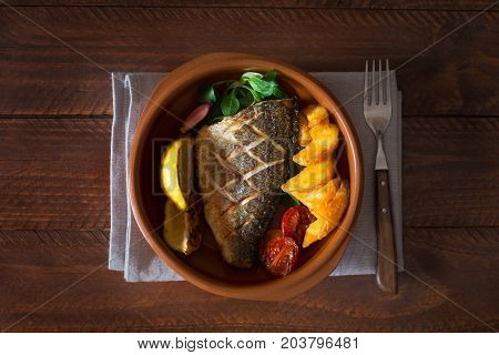 Baked dorado with fresh salad, vegetables and potato chips. This fish is a well-known in Spain and Turkey. It has high nutritional value, tender white meat and pleasant taste