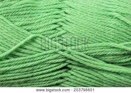 A super close up image of sage green yarn