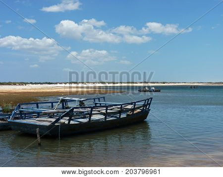 Blue boat waiting for tourists on a side of Lagoa Paraiso (Paradise Lagoon). Turquoise lagoon and white dunes in the distance. Picture was taken in Jericoacoara Brazil