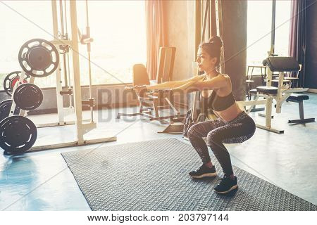Deep Squat Of Young Beautiful Woman In Sportswear Doing Squat While Standing In Front Of Glass At Gy