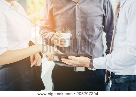 Group Of Business People Talking With Businessman Working On Digital Tablet In Outdoor After Work