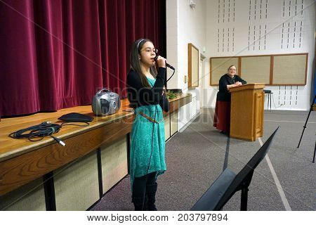 JOLIET, ILLINOIS / UNITED STATES - DECEMBER 28, 2015: A voice student sings a music recital at the Church of Jesus Christ of Latter-day Saints.