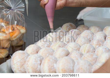 business bakery closeup hand work fresh donut jam background