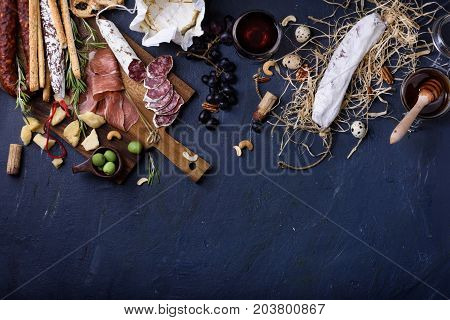 Appetizer italian antipasto Ham Olives Cheese Grissini bread sticks Sausage on dark blue background copy space. Top view copy space.