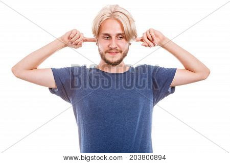 Stressful unpleasant situation conflict. Young man plug closing ears with hands protecting from loud noise. Guy not want to hear isolated on white