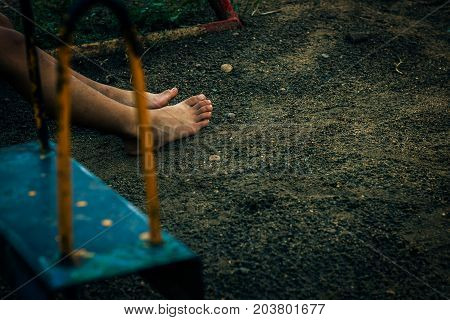 Children sitting in the playground, Swings in the playground outdoors close up.