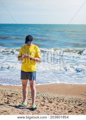 The man in the yellow shirt with headphones and the clock is Jogging. The concept of sports in the fresh air by the sea.