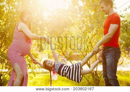 Family. Husband pregnant wife and daughter outdoors. Walk in the city park. Family fools around. Happiness of parenthood