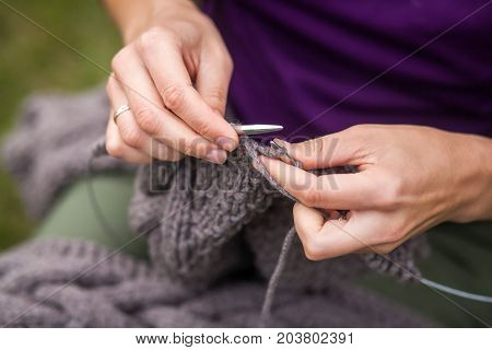 Close-up A young cheerful woman in a purple sweater knits with knitted needles of a natural Italian wool cardigan in the background a green grass top view