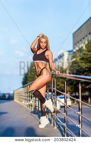 Young sportive woman fitness bikini with light afro pigtails i in black sportswear posing against a background of cityscape on a summer day