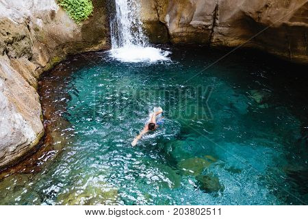 Man swimming in turquoise and crystal clear water near small waterfall in Sapadere canyon near Alanya of Turkey