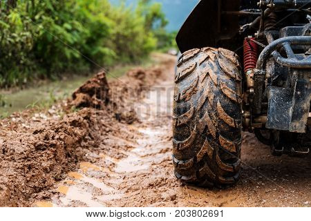 Off road wheel on dirt road in rainy day