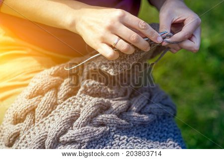 Close-up A young cheerful woman in a purple sweater knits with knitted needles of a natural Italian wool cardigan in the background a green grass