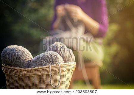 Wicker basket with brown threads made of natural wool in the background a woman in a purple sweater knits a sweater
