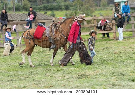 June 3 2017 Machachi Ecuador: a child and a cowboy walking with a horse outdoors in the Andean town