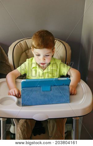 Portrait of cute adorable white Caucasian toddler boy sitting in high feeding chair playing watching digital tablet during meal. Lifestyle early development. New technology generation.