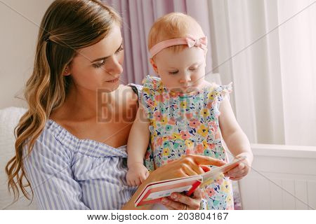 Portrait of beautiful young white Caucasian mother and little girl daughter reading book together indoors at home. Parent with child doing family activity. Lifestyle concept