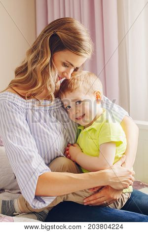 Group portrait of beautiful young white Caucasian mother and preschooler child boy playing together on bed in bedroom. Mom with son hugging cuddling indoors at home. Natural family lifestyle