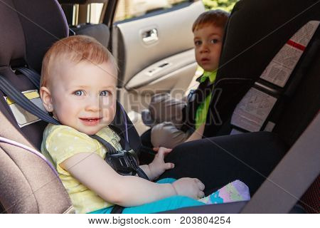 Portrait of two cute white Caucasian toddlers childen sitting in car seats looking in camera. Smiling babies in automobile vehicle fastened with seatbelts.