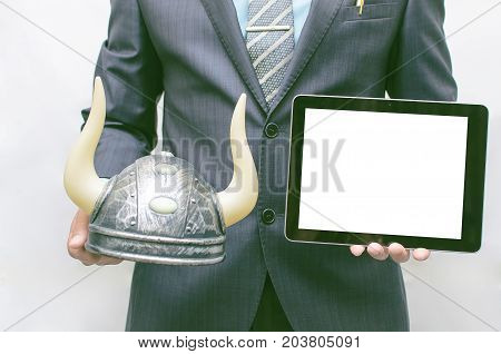 Stock broker. Bull speculation concept. Agressive business strategy. Business man holding a bull hat with horns in hand and tablet computer with blank screen in another hand. Financial product presentation.