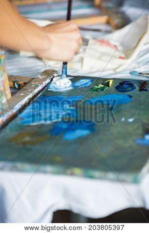 close-up of artist mixes oil paints on pallet. oil paint brush in hand