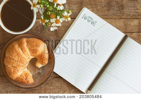 Homemade croissant served with black coffee or americano. Delicious breakfast with fresh croissant and coffee. Croissant and black coffee with open notebook and pencil in top view or flat lay style. Coffee and croissant for coffee break.