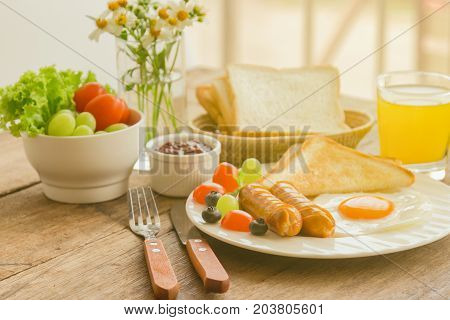 Homemade breakfast with sunny side up fried egg toast sausage fruits vegetable strawberry jam and orange juice in side view with copy space. Delicious homemade american breakfast concept for background. American breakfast for family.