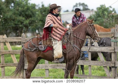 June 3 2017 Machachi Ecuador: cowboy in traditional poncho and chaps on horseback