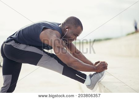 Male Runner In Black Sportswear Stretching Legs Before Doing Morning Workout.
