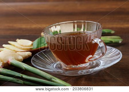 An image of ginger juice and fresh ginger with green leaves isolated on wooden background.