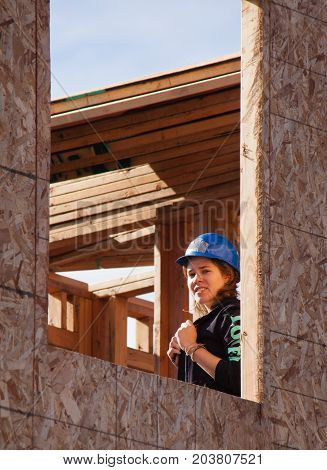 Oakland Calif - Jan 22 2011: Woman looks out unfinished window of home for Habitat For Humanity. El Rincon