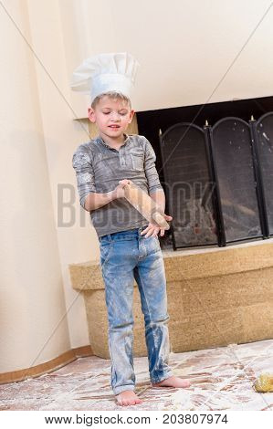 Cutest boy in chef's hat near the fireplace standing on the kitchen floor soiled with flour playing with food making mess