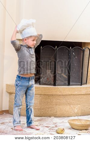 Funny boy in chef's hat near the fireplace standing on the floor soiled with flour playing with food making mess around himself