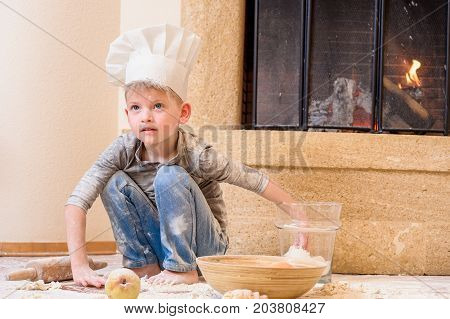 A boy in chef's hat near the fireplace sitting on the kitchen floor soiled with flour playing with food making mess all around