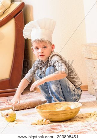 A boy in chef's hat near the fireplace sitting on the floor totally soiled with flour playing with food making mess and having fun