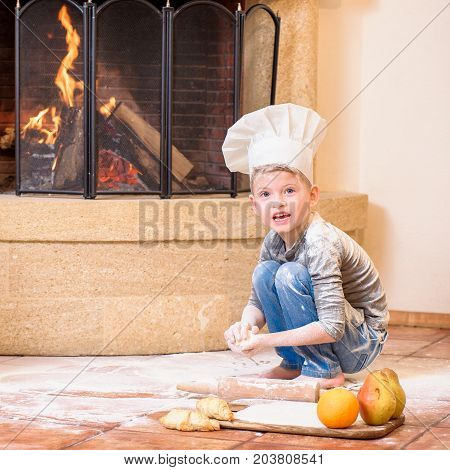 A boy in chef's hat near the fireplace sitting on the kitchen floor soiled with flour playing with food making mess. Looking at camera