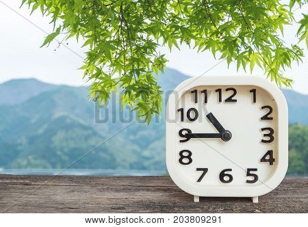 Closeup white clock for decorate show show a quarter to ten o'clock or 10:45 a.m. on blurred green leaves and mountain view background