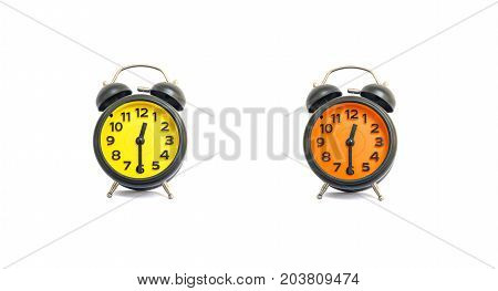 Closeup yellow alarm clock and orange alarm clock for decorate show a half past twelve o'clock or 12:30 p.m. isolated on white background