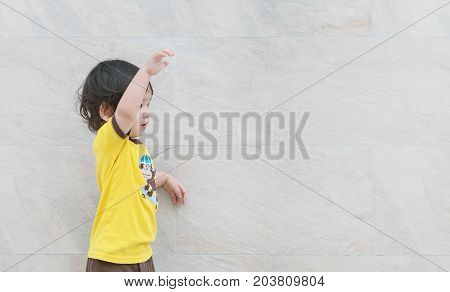 Closeup cute asian kid look at the space with beckon someone action on marble stone wall textured background