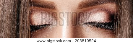 close-up of a beautiful tanned woman with perfect make-up. pink eye makeup