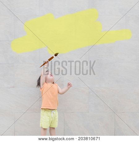 Closeup cute asian kid use paintbrush paint yellow color for text box at the marble stone wall textured background