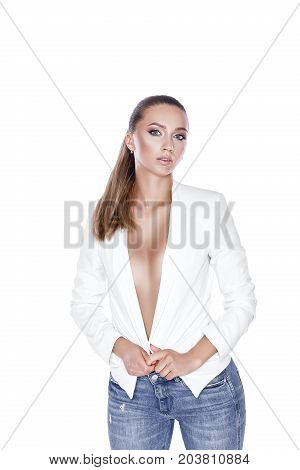 beautiful sexy tanned brunette woman with perfect makeup in white jacket and jeans posing in front of camera