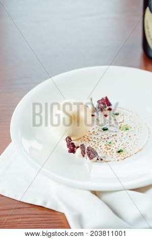 Sweet Dessert With Ice Cream Ball, Sugar Candy, Fruit And Mint On White Plate