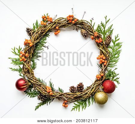 Christmas wreath of grape vines with decorative balls thuja branches rowanberries and cones. Festive DIY wreath. New Year round wreath on white background. Flat lay top view
